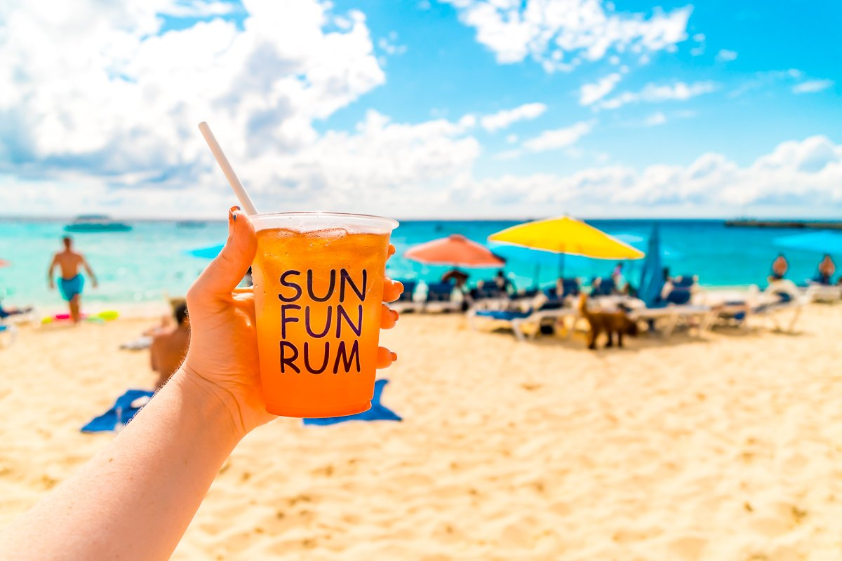 Woman's hand holding a cup of rum punch on a beach in front of beach umbrellas.