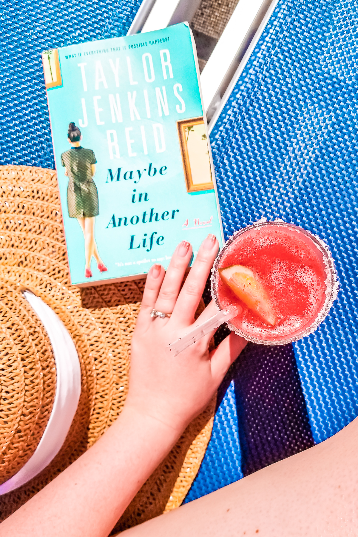 Sunhat, book, and frozen cocktail sitting on a blue lounge chair.