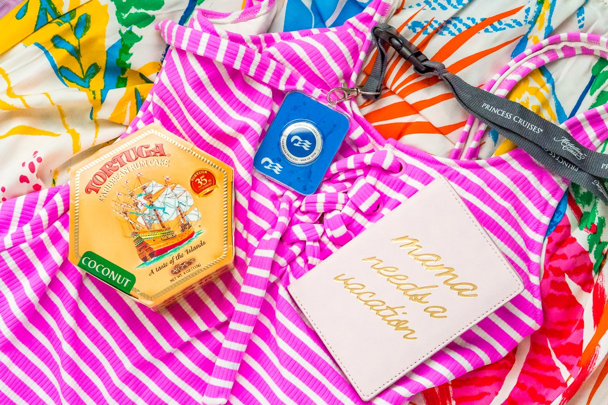 Rum cake, princess medallion, and passport laying on a pink and white striped bathing suit.