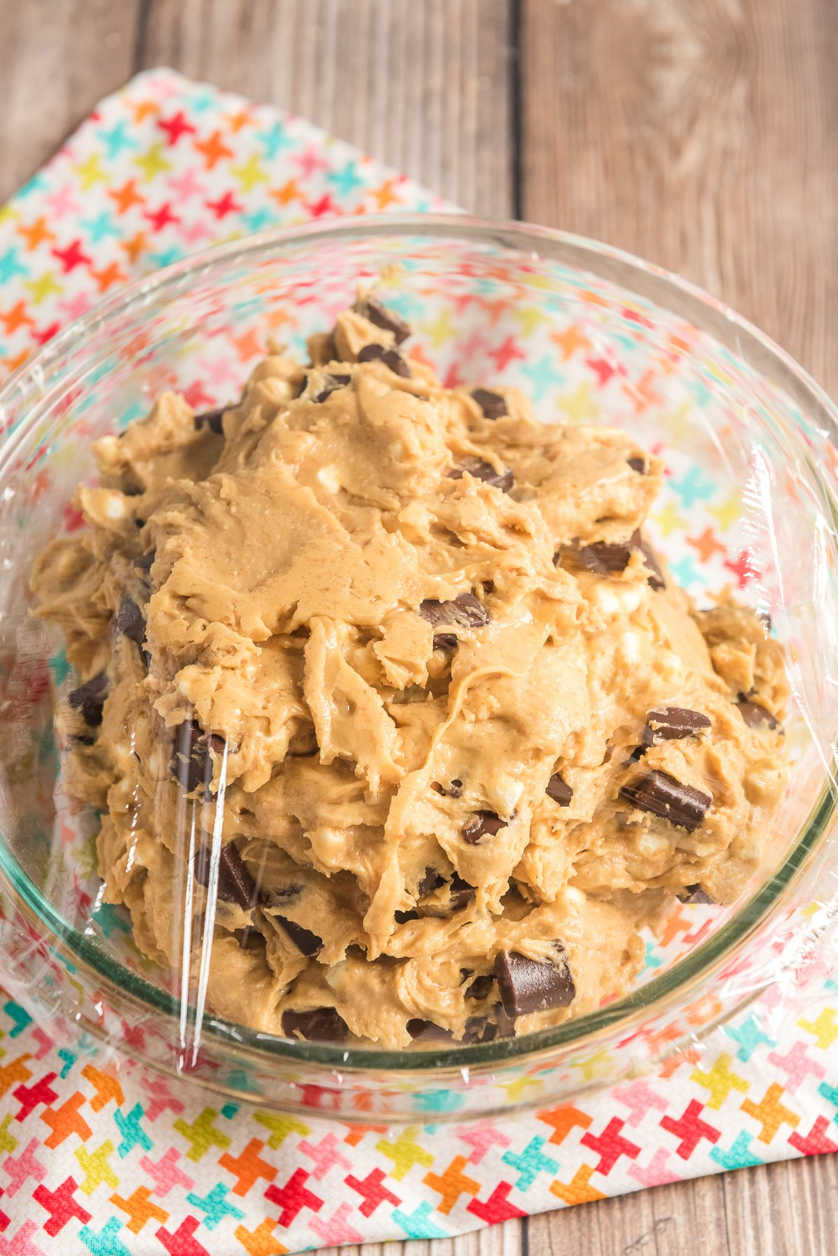 Cookie dough in a glass mixing bowl covered with plastic wrap.
