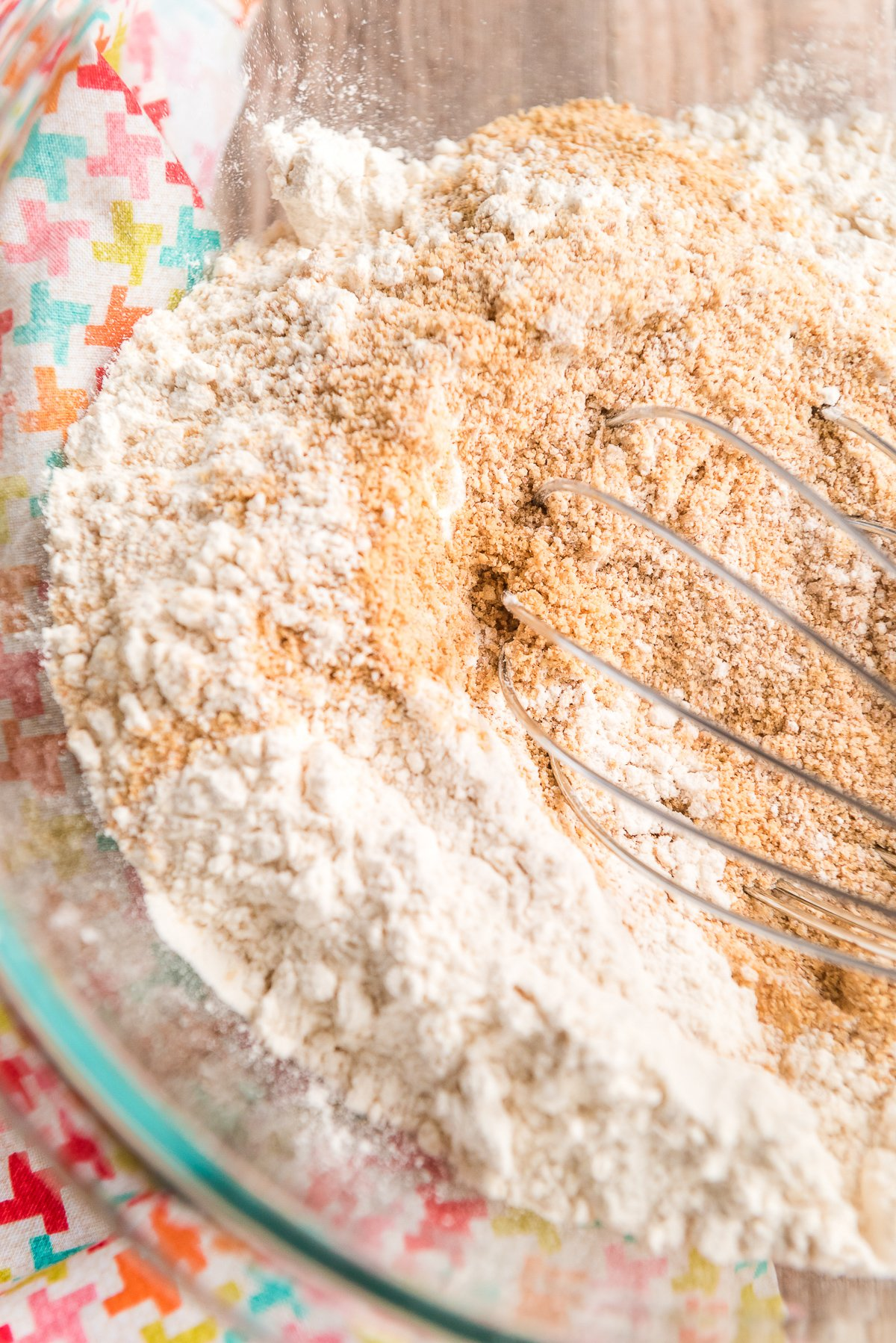 Flour and graham cracker crumbs being whisked together in a glass bowl.