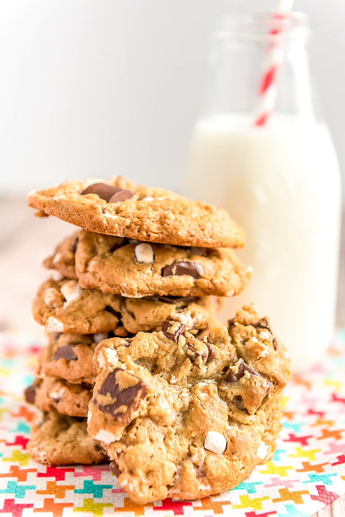 Stack of cookies with marshmallows and chocolate chunks in front of a glass of milk. One cookie is leaning against the others.