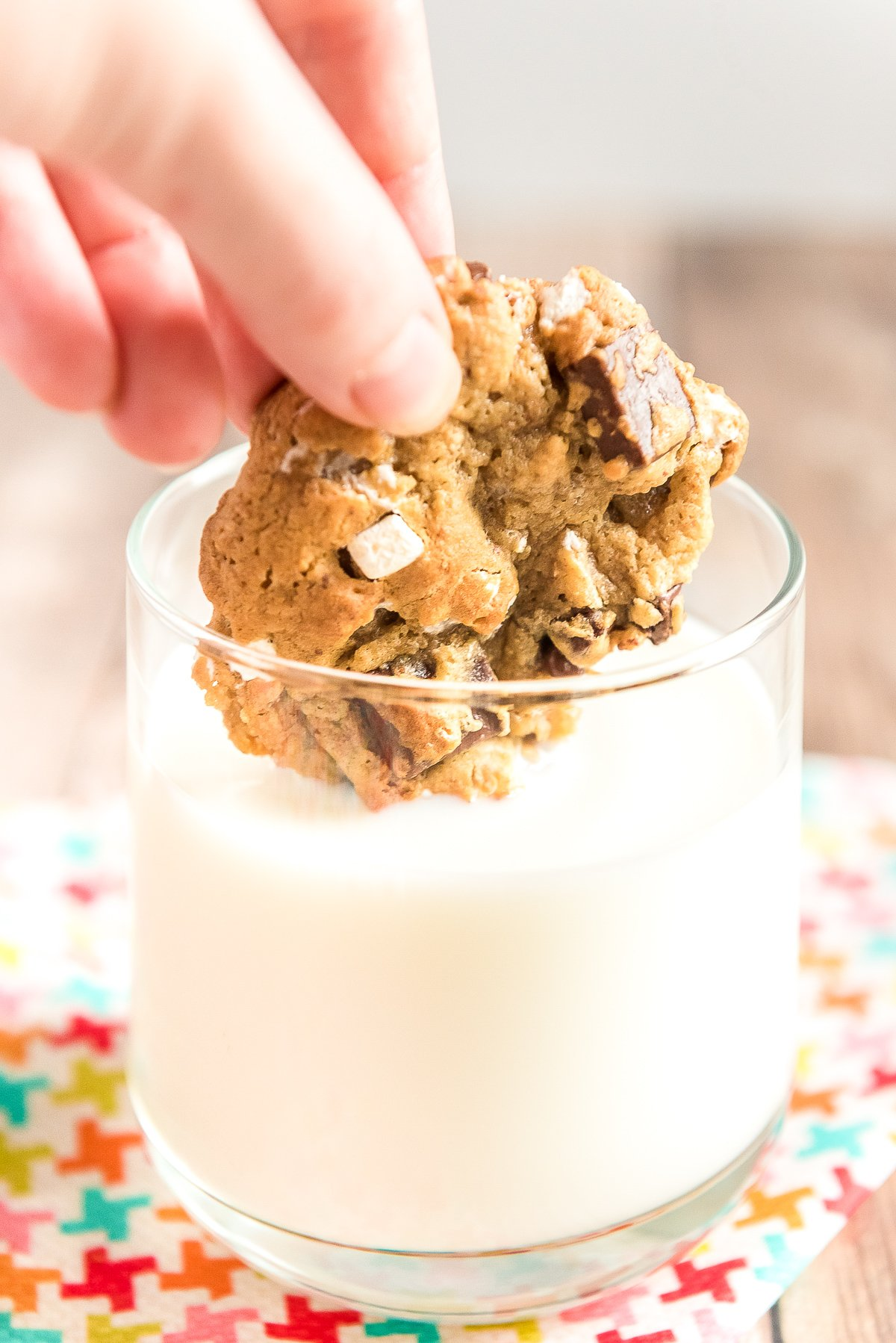 S'mores cookie being dunked in a glass of milk.