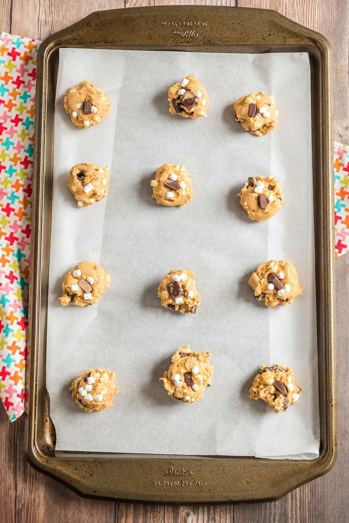 Cookie dough balls on a parchment lined cookie sheet.