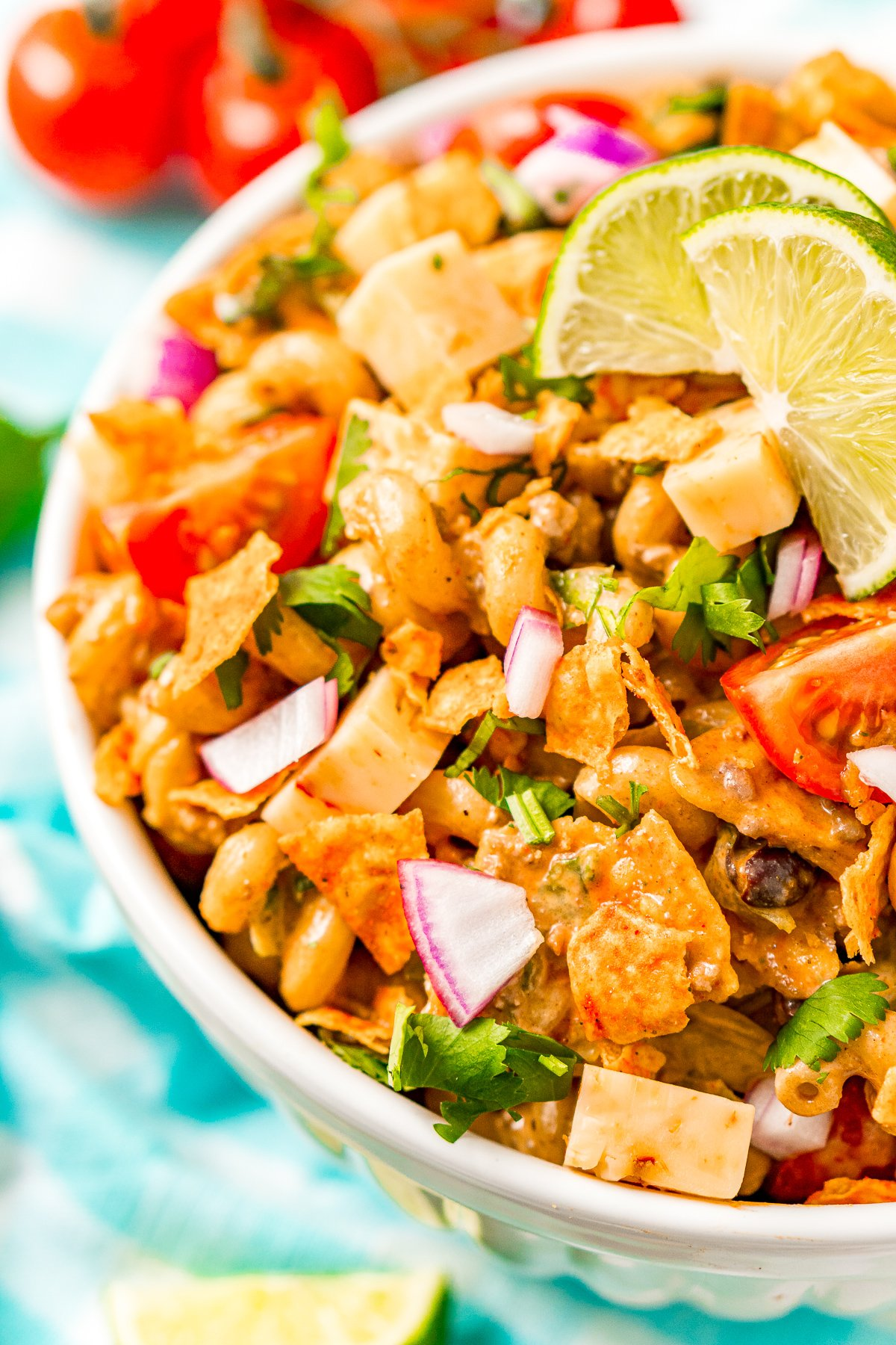 Pasta salad with taco fixings in a large white bowl for serving.