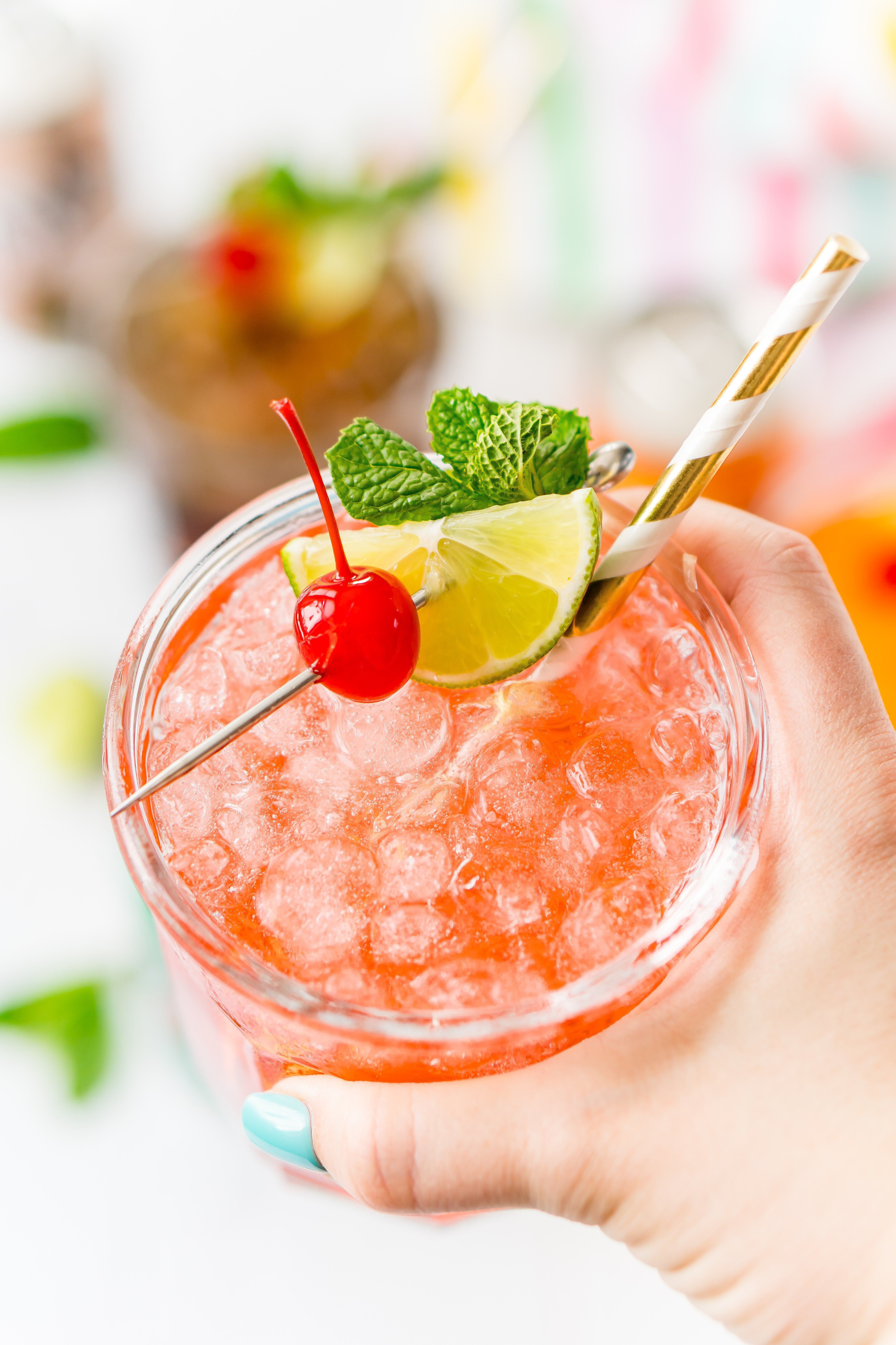 Woman's hand holding up a drink garnished with cherry, mint, and lime.