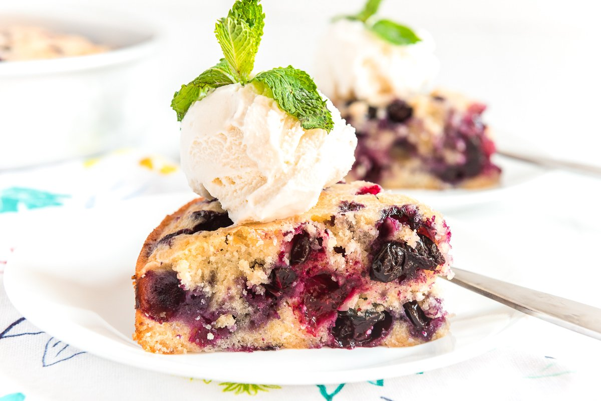 Slice of blueberry snack cake on a white plate topped with ice cream and garnished with mint.