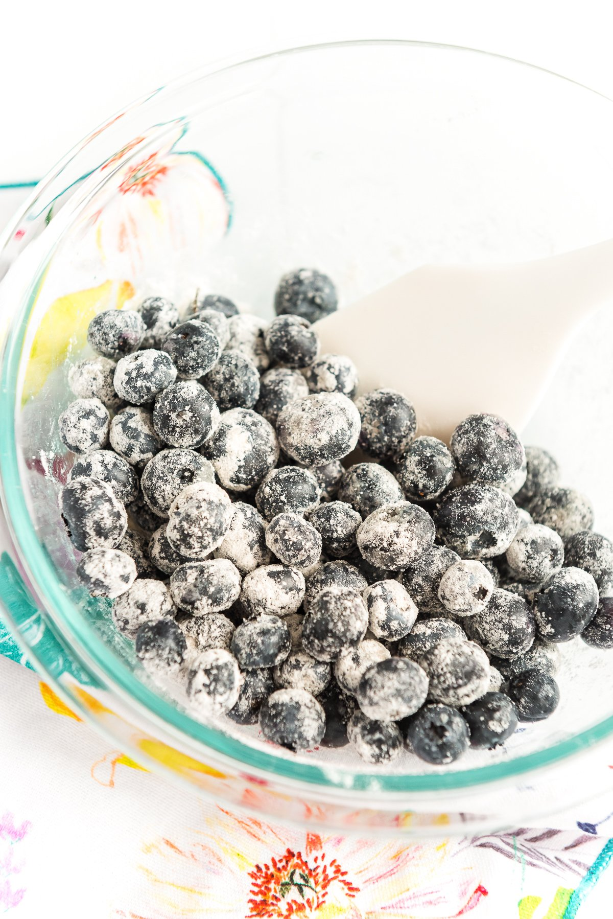 Blueberries being tossed with flour in a large glass bowl.