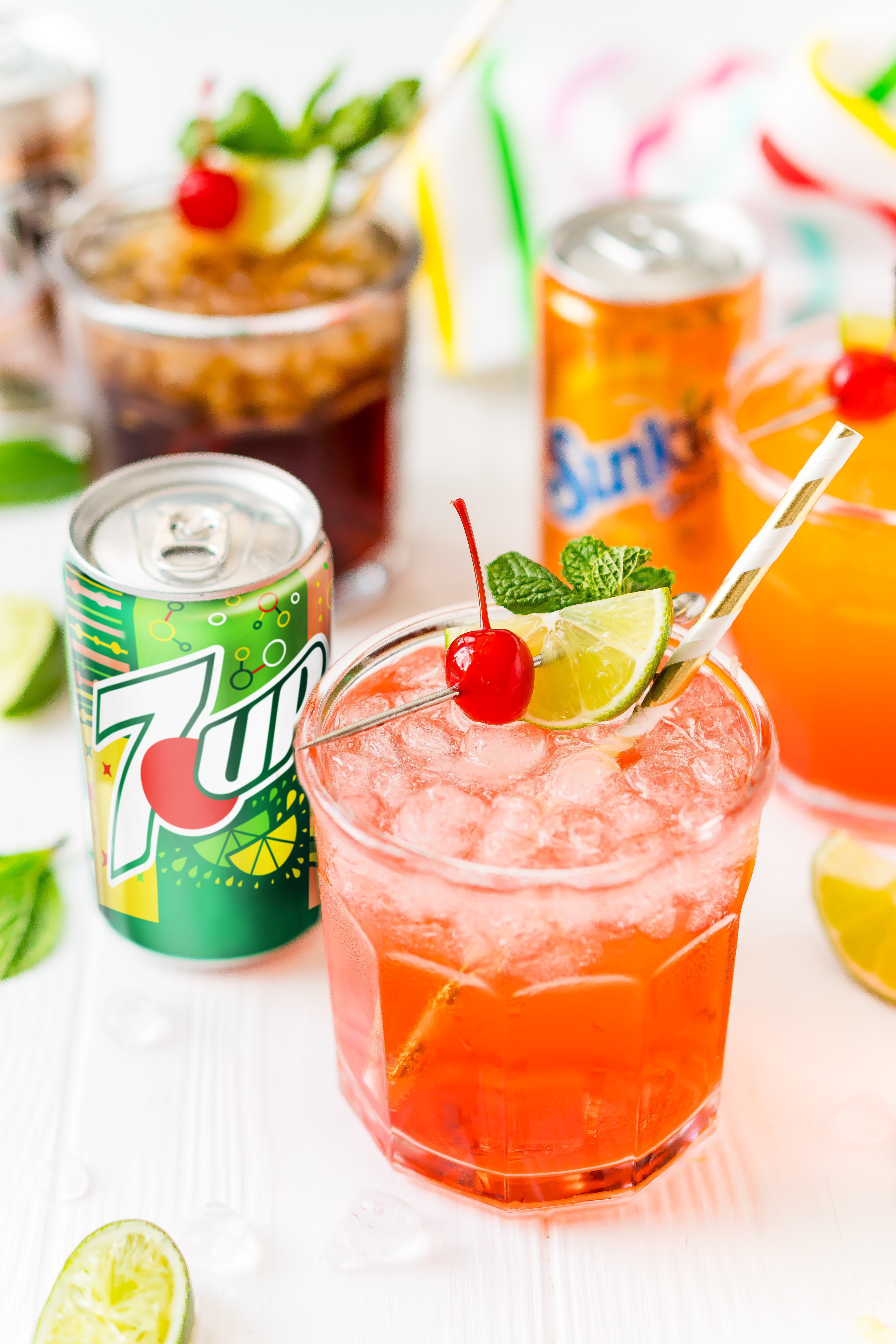 Mocktail in a glass with a can of 7UP next to it and more drinks in the background.