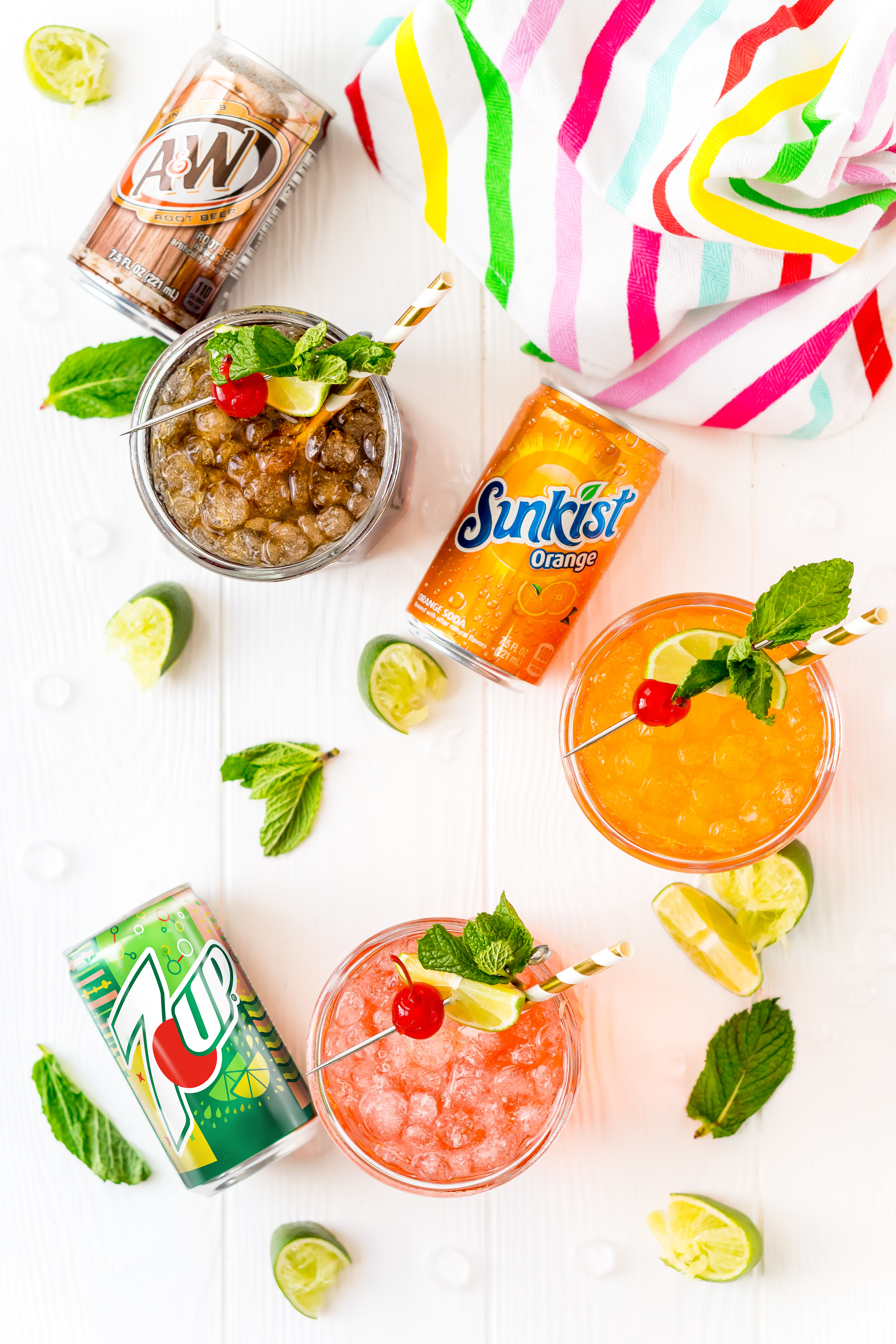 Overhead shot of drinks with cans of soda next to them with lime wedges.