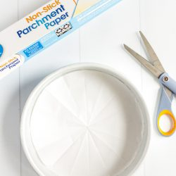 Parchment paper lined cake pan with a roll of parchment paper and pair of scissors next to it.