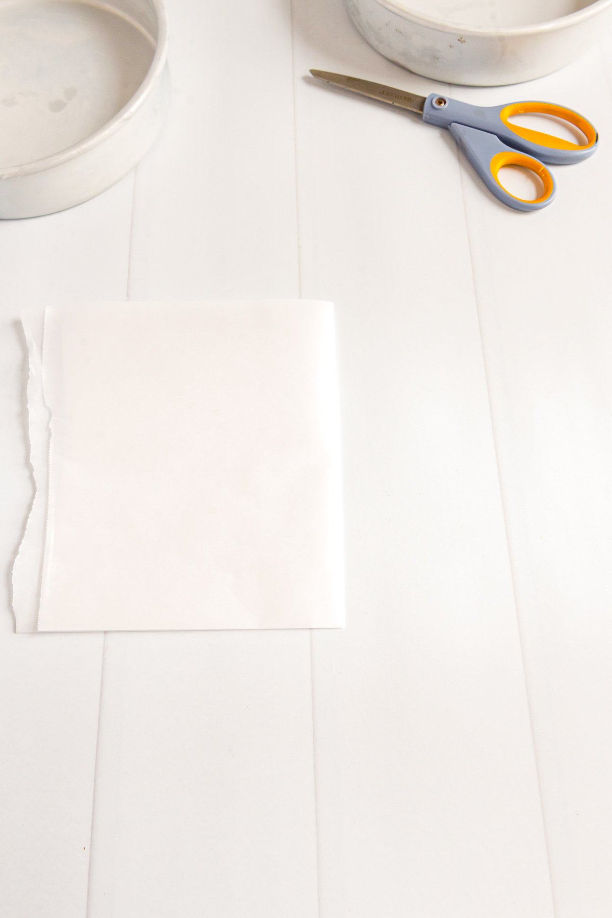 Piece of parchment paper folding in half with cake pans and scissors on the table.
