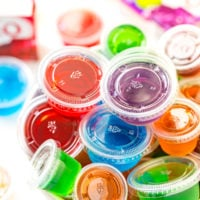 Multi colored jello shots in a white bowl.