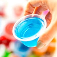 Woman's hand holding a blue jello shot.