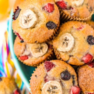Muffins with banana and berries piled in a teal bowl.