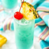 Angled close up photo of a blue hawaiian cocktail garnished with a pineapple edge and cherry.