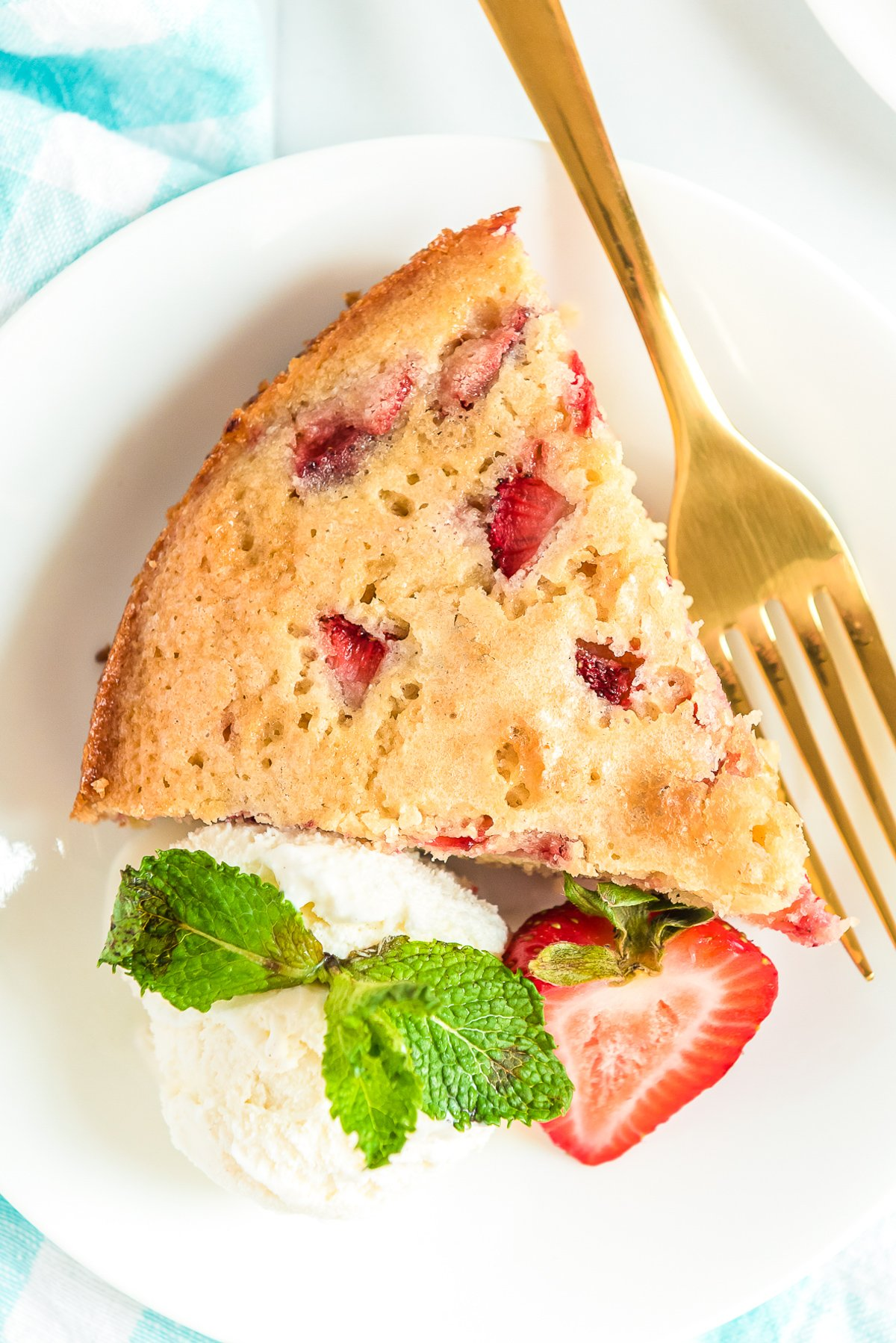 Overhead photo of a slice of strawberry cake on a white plate with whipped cream and gold fork.