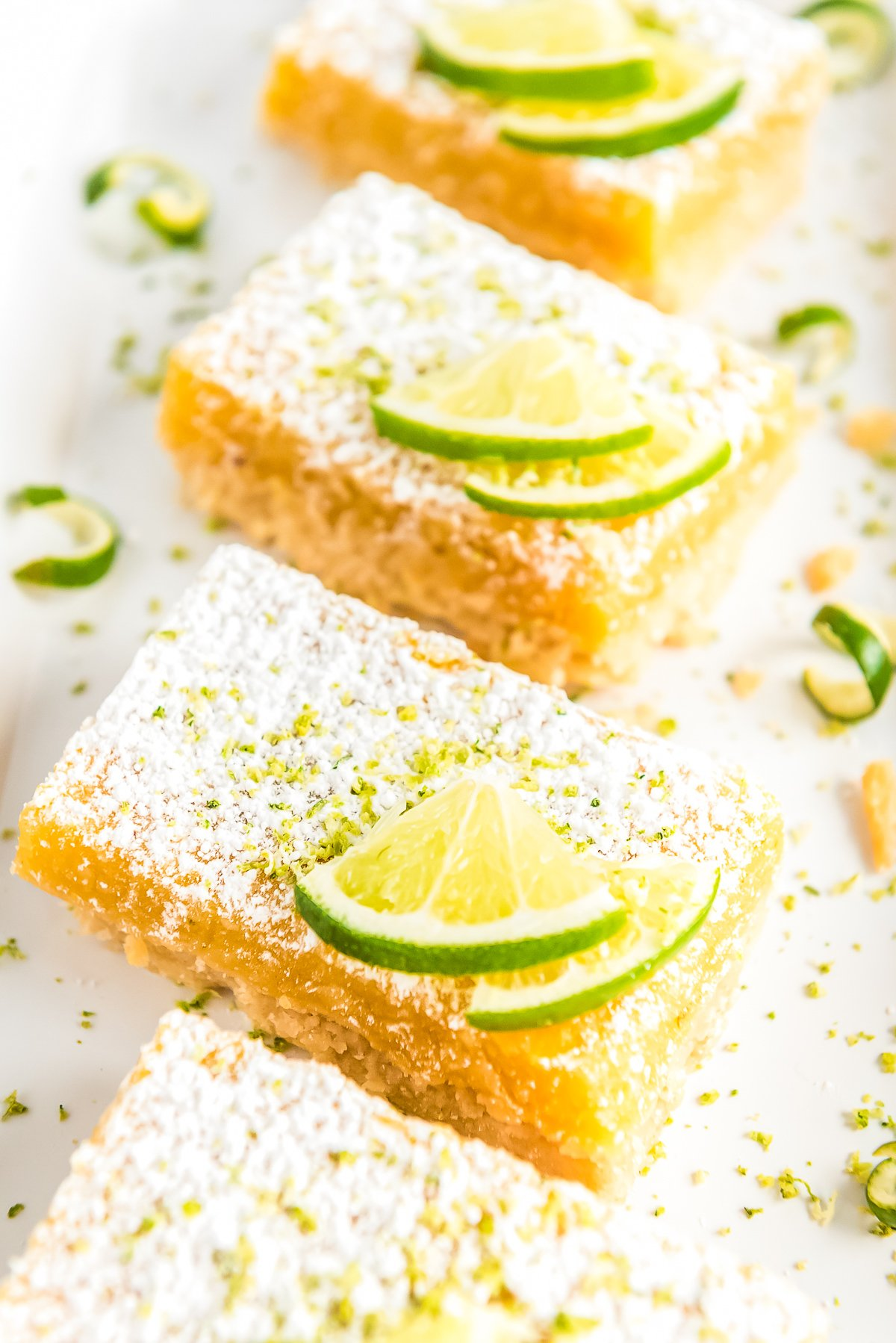 Lime Bars lined up on a white plate topped with lime wedges and powdered sugar.