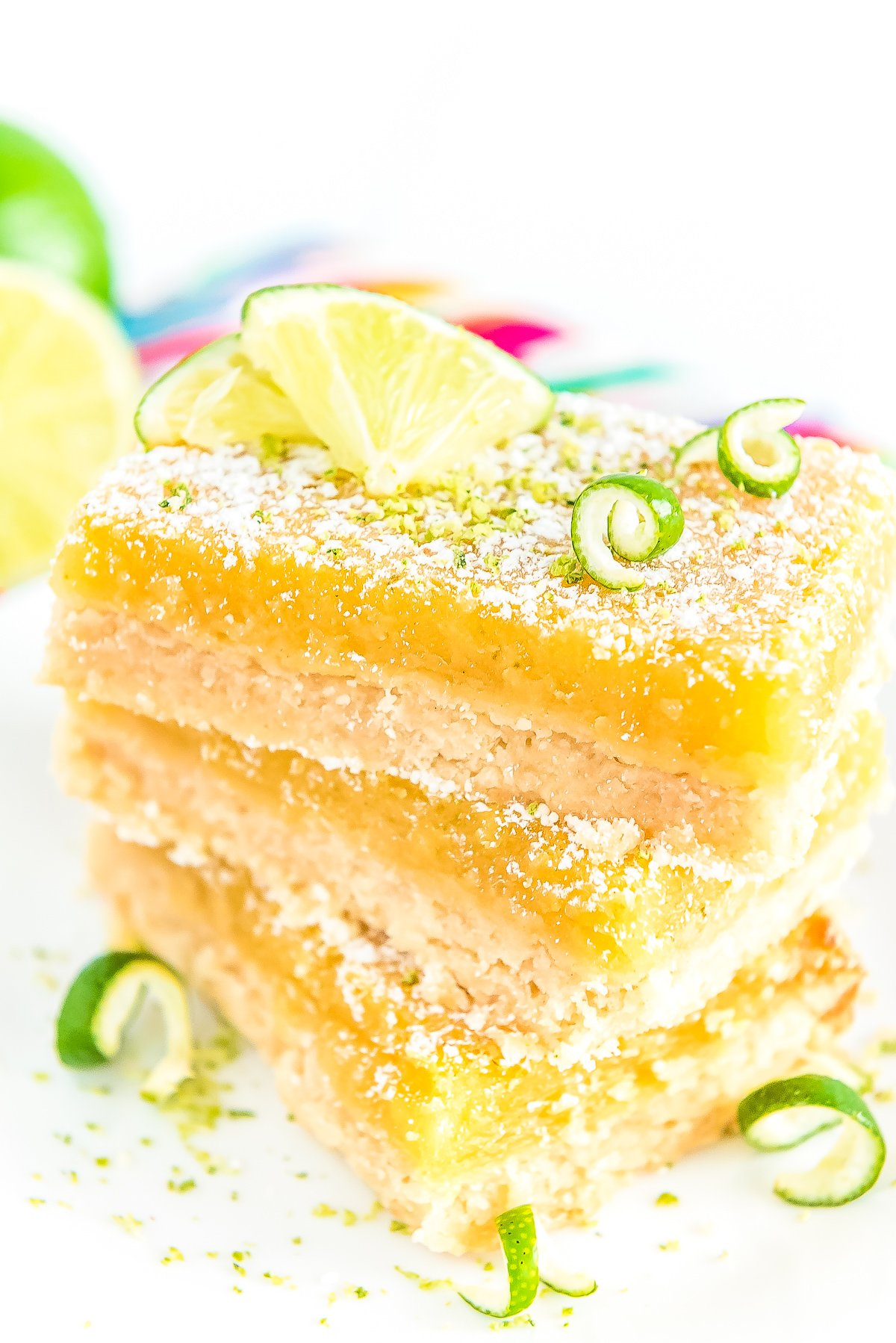Stack of Key Lime Bars on a white plate garnished with powdered sugar and lime zest.