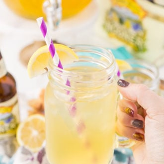 Woman's hand holding a lemonade shandy in a handled mason jar.