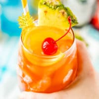 Woman's hand holding a glass filled with a rum runner cocktail garnished with orange, pineapple, and cherry.