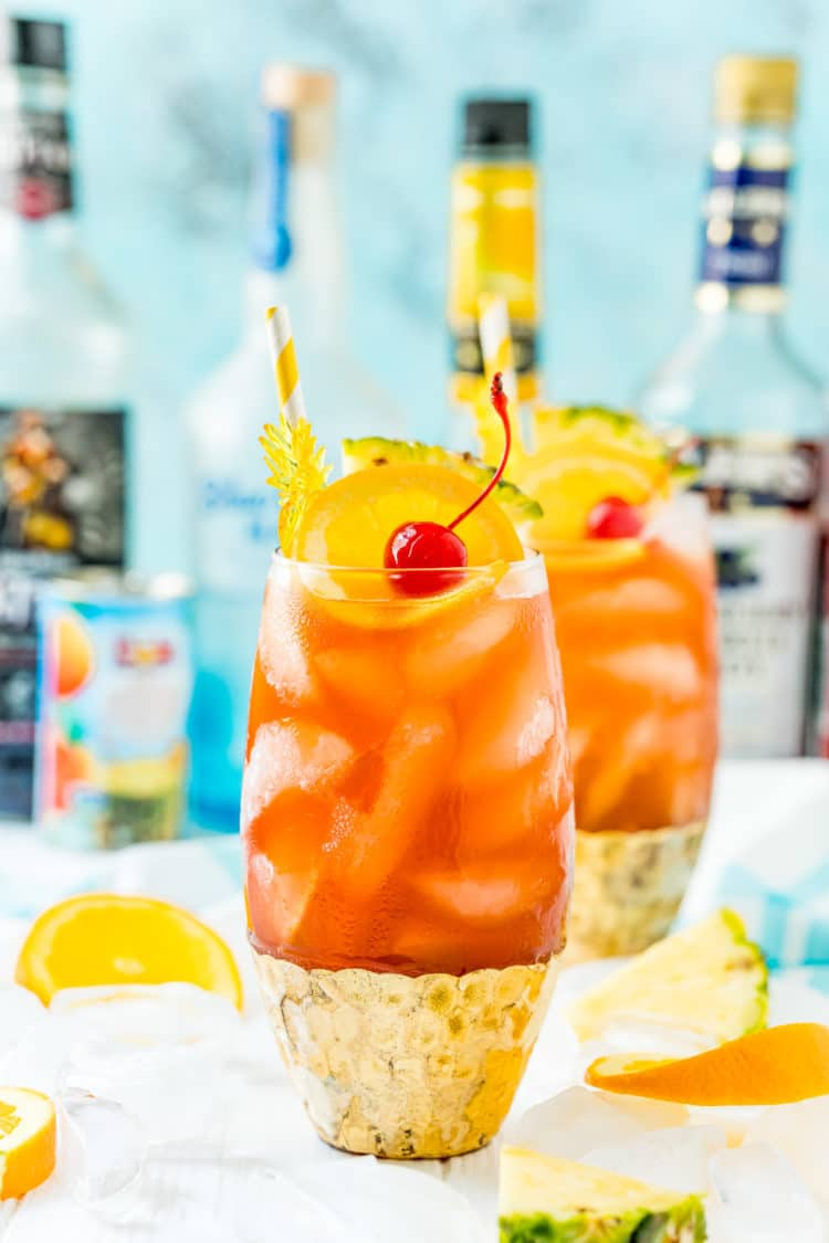Photo of a rum runner cocktail with another drink and bottles of liqueur behind it.