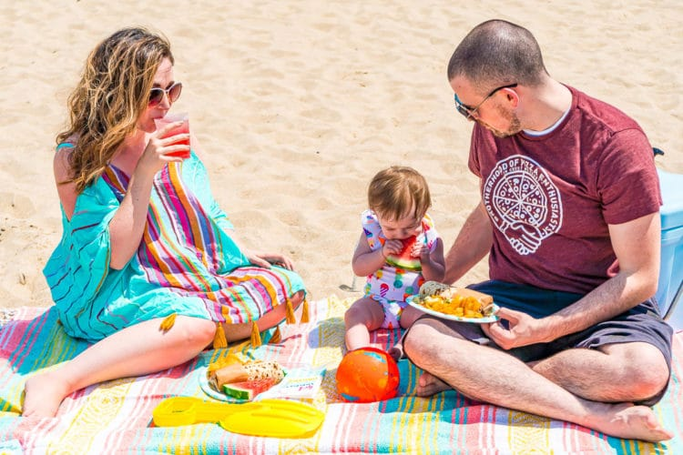 Family of three enjoying a picnic on the beach in the summer.