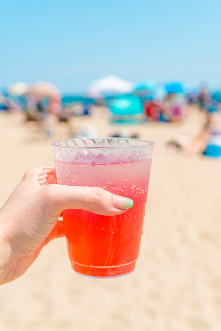 Woman's hand holding a cup of Cranberry Lemonade at the beach.