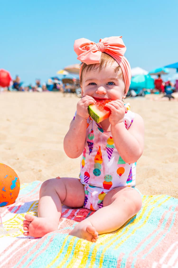 Baby girl eating watermelon at the beach.