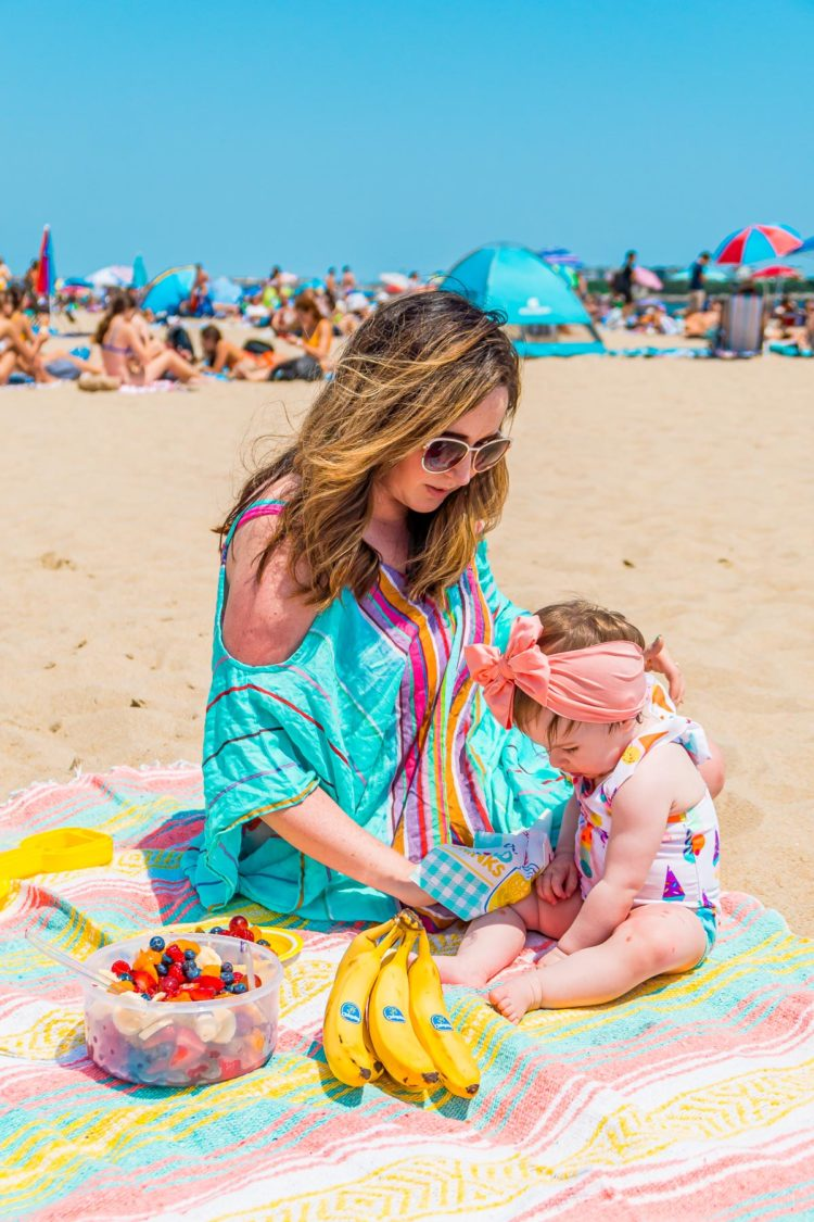 Mother and infant daughter having a picnic on the beach.