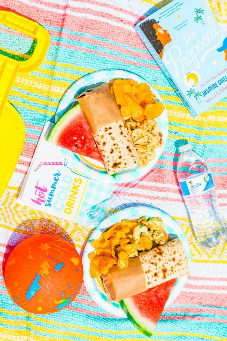 Beach picnic spread with food, napkins, books, and beach toys.