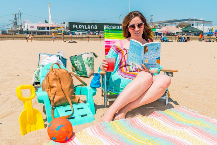 Woman sitting in a beach chair reading and drinking a lemonade.