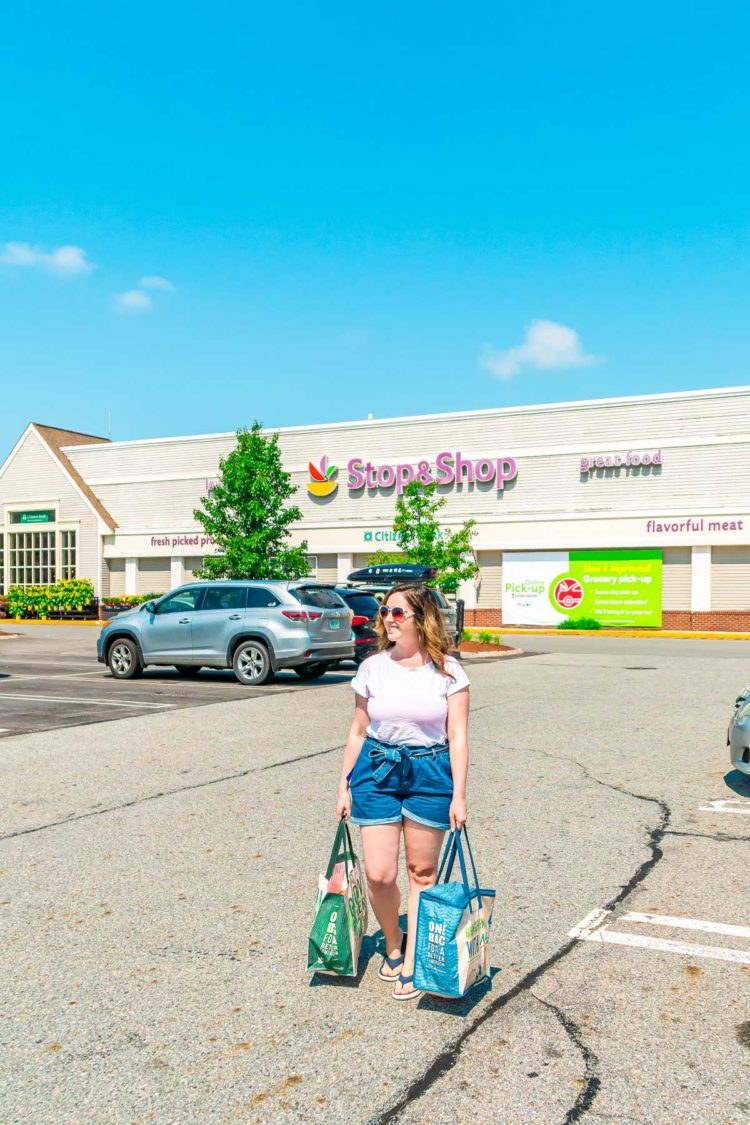 Woman carrying grocery bags out of a Stop & Shop grocery store.
