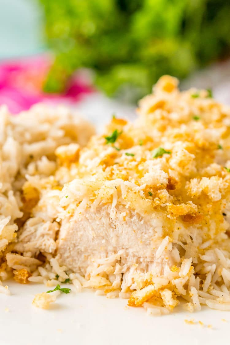 Close up photo of a baked chicken breast that has been cut into. Crusted with croutons and served with rice.