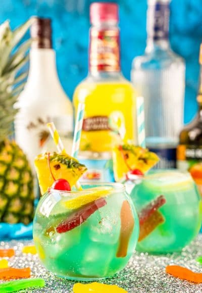 Fish bowl cocktail with pineapple and bottles of alcohol in the background.