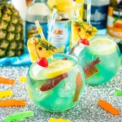 Individual fish bowl drinks with bottles of alcohol in the background.