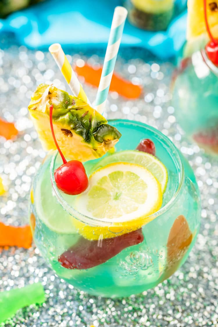 Close up photo of a fish bowl drink on a silver sparkling table.