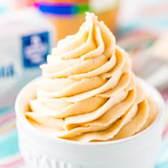 Close up photo of peanut butter cream cheese frosting piped into a small white bowl.