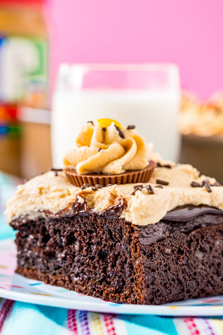 Close up photo of a slice of chocolate cake with peanut butter frosting on a white plate with a glass of milk in the background.