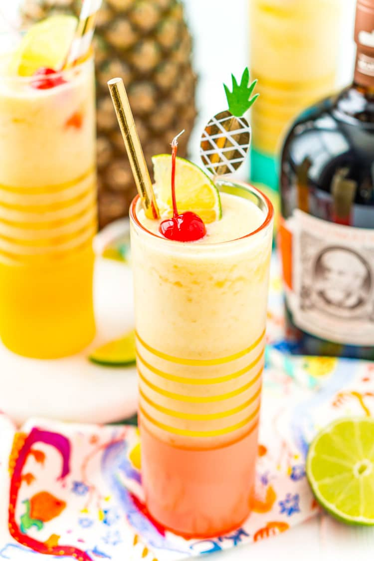 Two glasses filled with a frozen cocktail with a bottle of rum and a pineapple in the background.