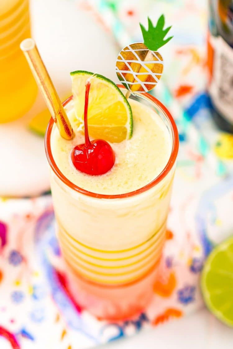 Close up photo of a pineapple daiquiri garnished with a maraschino cherry, lime wedge, and gold straw.