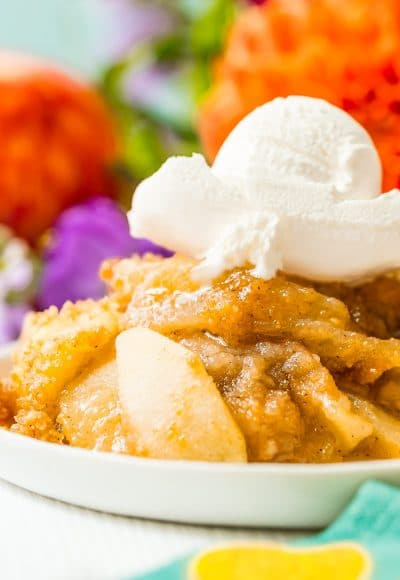 Close up photo of apple brown betty on a white plate topped with ice cream.