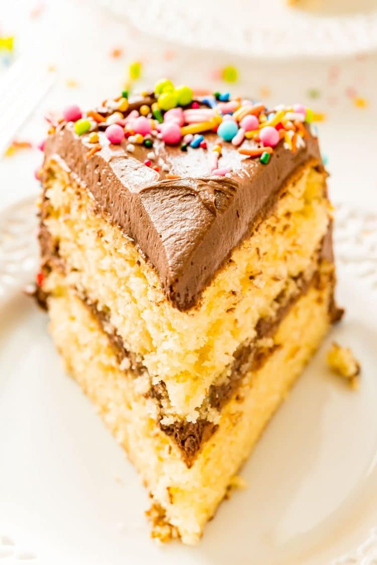 Slice of yellow cake with chocolate frosting and sprinkles on a white plate.