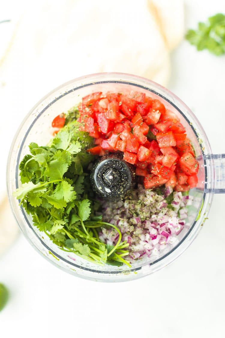 Herbs, onions, and tomatoes in a food processor.