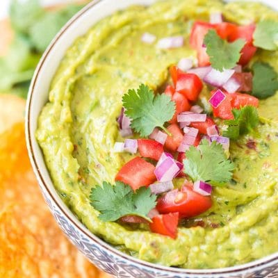 Close up photo of a bowl of guacamole garnished with diced tomatoes, cilantro, and red onion.