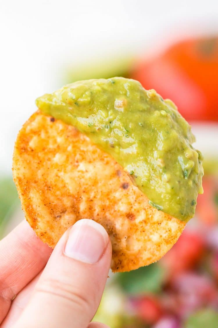 Woman's hand holding a tortilla chip that's been dipped in guacamole.