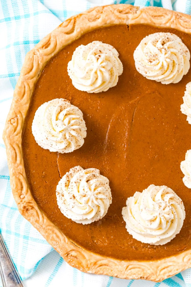 Overhead photo of a pumpkin pie topped with dollops of whipped cream.