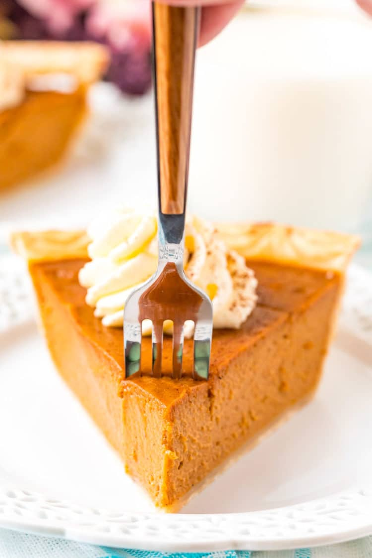 A fork taking a bite out of a slice of pumpkin pie.