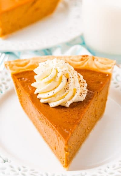 Close up photo of a slice of pumpkin pie on a white plate topped with whipped cream.