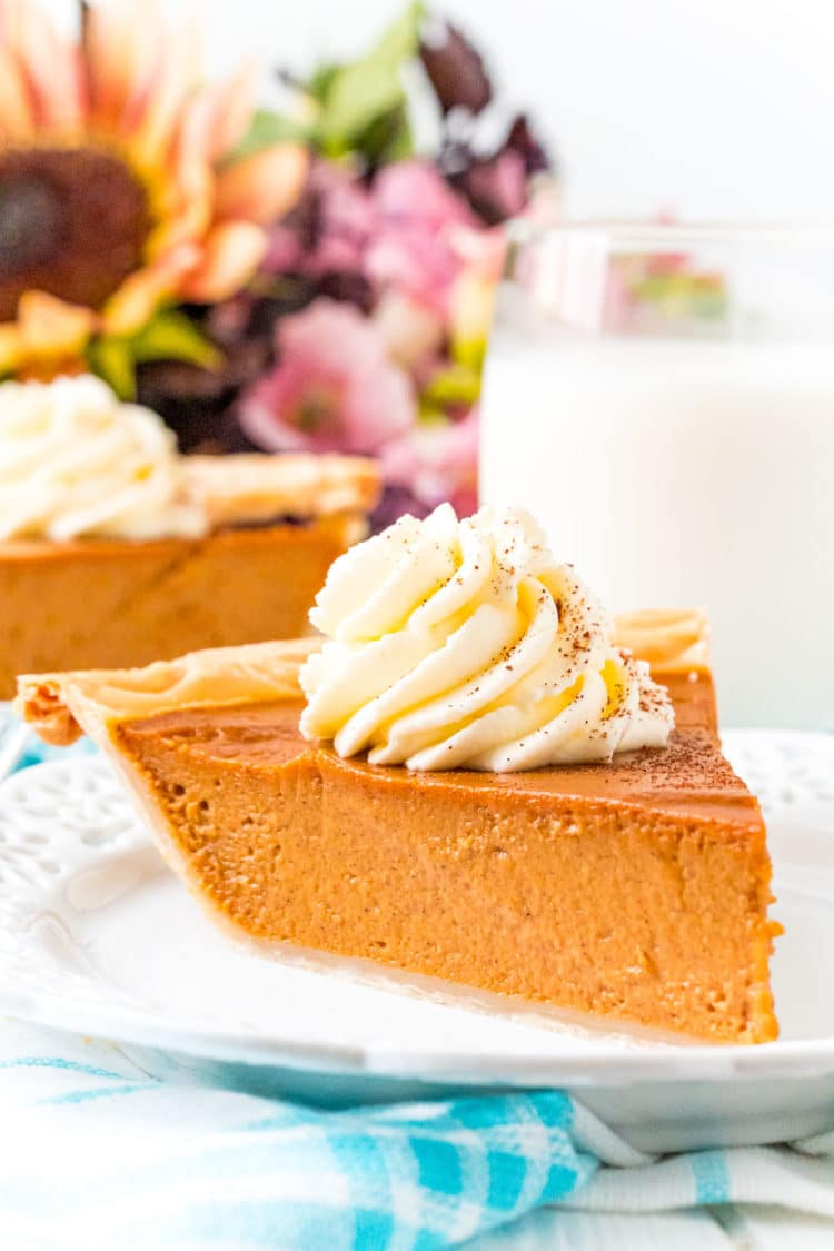 Photo of a slice of pumpkin pie on a white plate with a glass of milk and flowers in the background.
